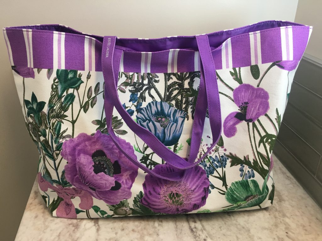 This adorable purple floral tote comes with the Estee Lauder tote.