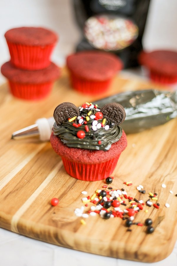 Place two Mini Oreo cookies on the sides for ears and sprinkle the top of the cupcakes with Mickey Mouse sprinkles.
